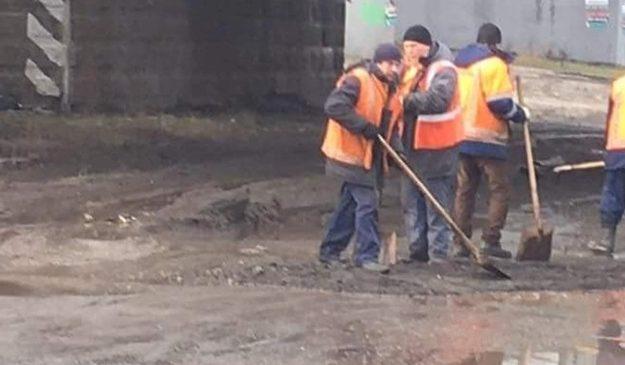 В Киеве коммунальщики латают дорогу и лужи им нипочем